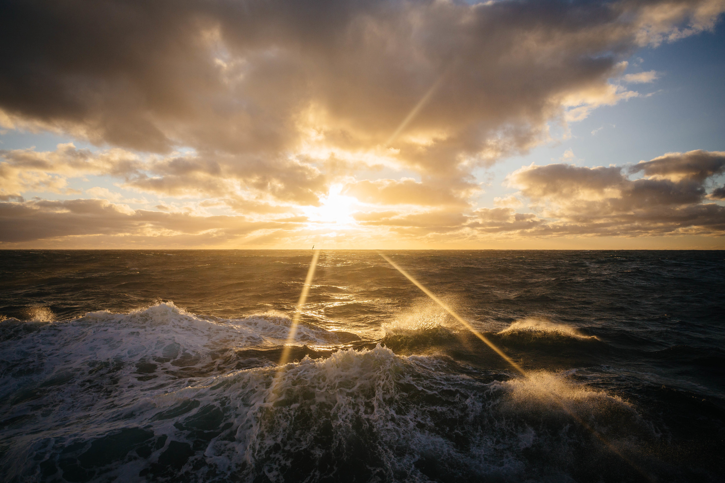 A golden sun sets and waves roll by as we sail south through the Drake Passage.