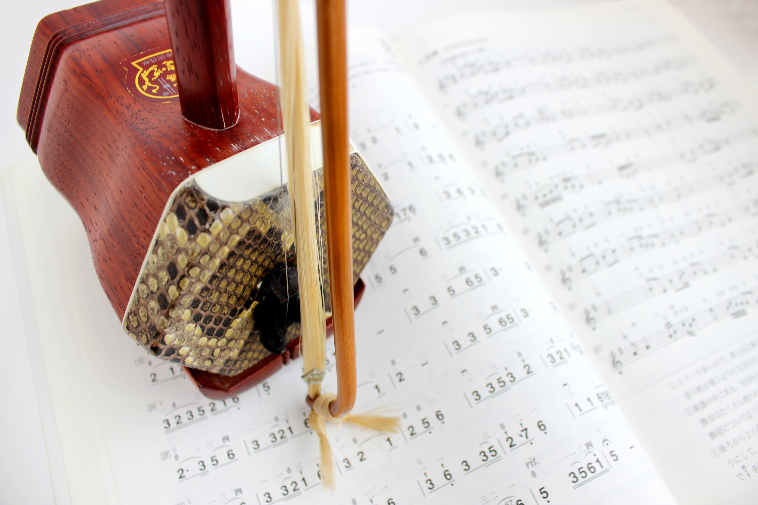 Erhu is a traditional Chinese musical instrument. It has two strings and is played with a bow between the strings. The sound box is usually covered with python skin. The background image is sheet music in jianpu musical notation.