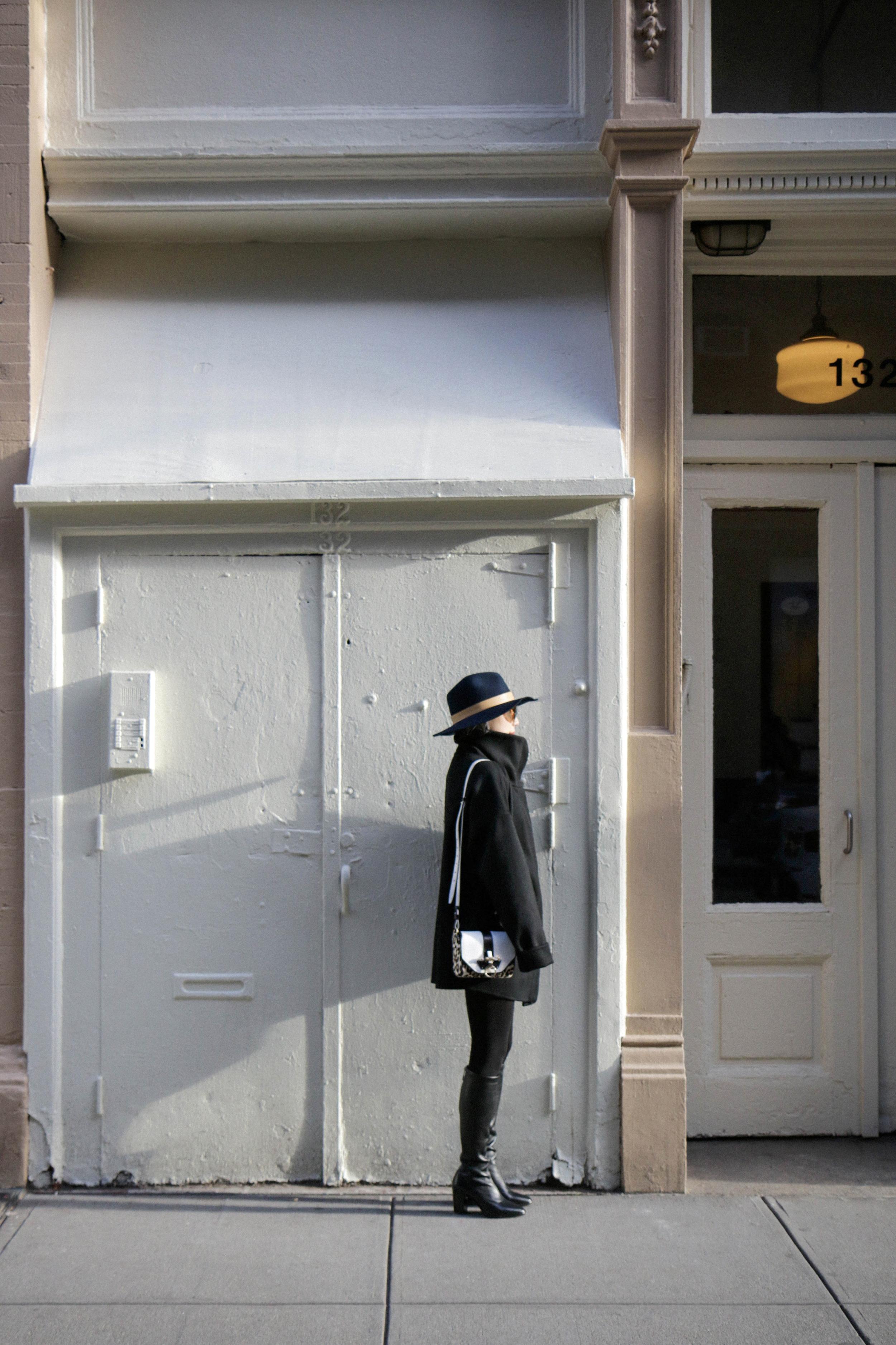 Stutterheim Stockholm Jacket ,  Michelle Waugh Coat ,  Won Hundred Sweater ,  Acne Studios Shirt ,  Wolford Tights , Balenciaga Boots, Givenchy Bag,  Janessa Leone Hat ,  Illesteva Sunglasses ,  Catbird Rings