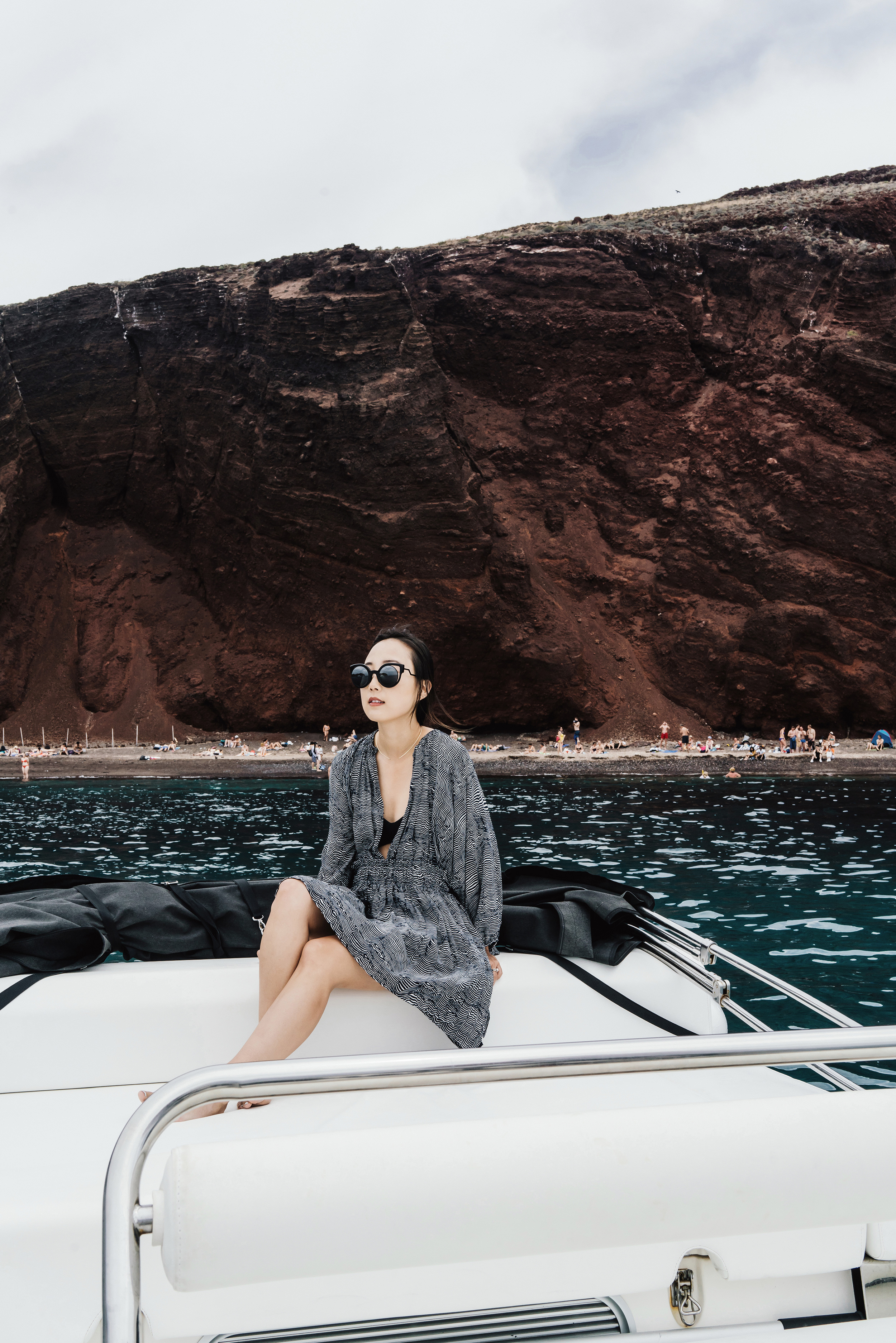 Apiece Apart Dress ,  Her The Label Swimsuit ,  Fendi Sunglasses  in front of Red Beach
