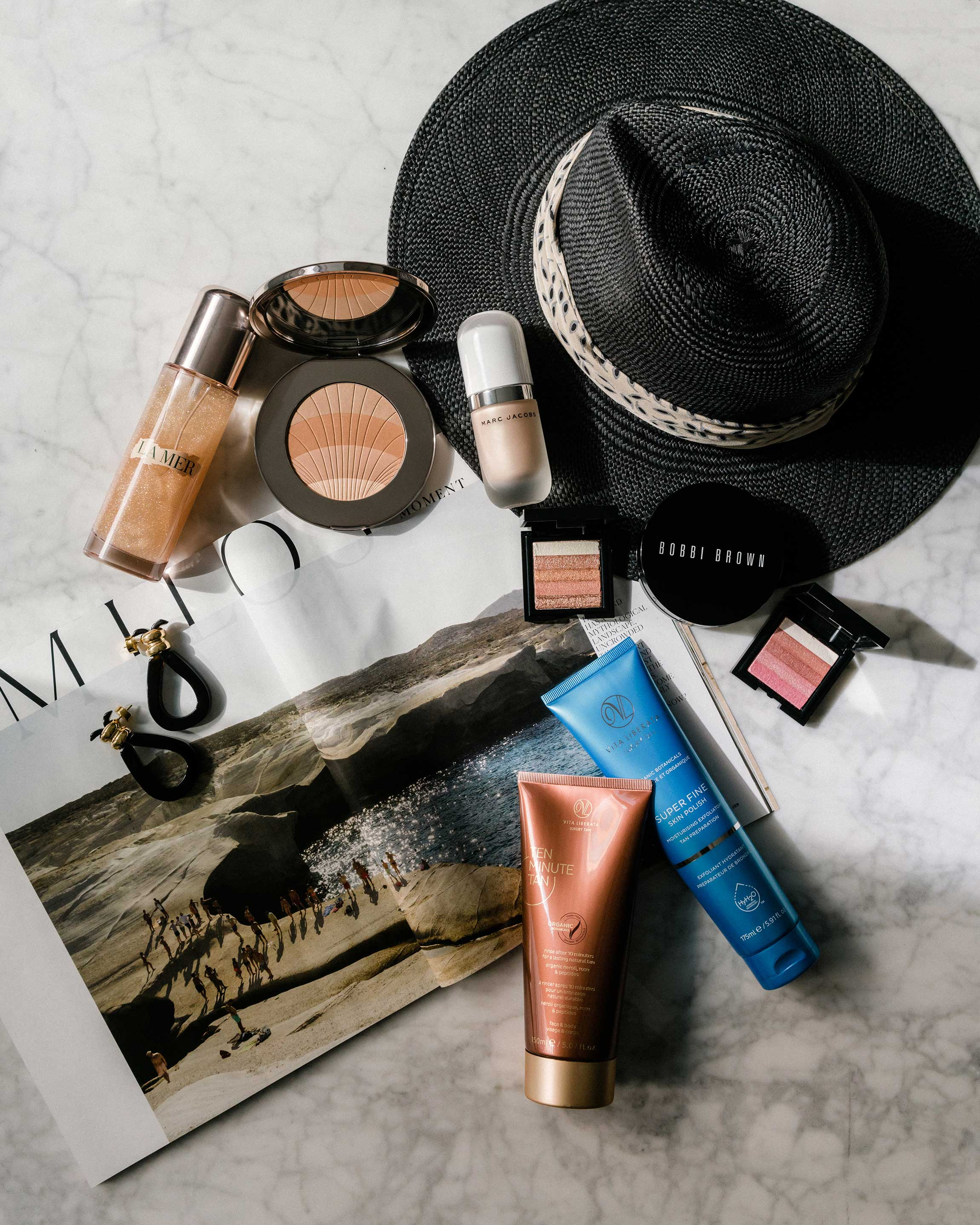 La Mer Body Oil  and  Bronzing Powder ,  Marc Jacobs Highlighter ,  Bobbi Brown Cushion Compact  and  Powders ,  Viva Liberta Tan  and  Scrub ,  Loewe Earrings ,  Janessa Leone Hat