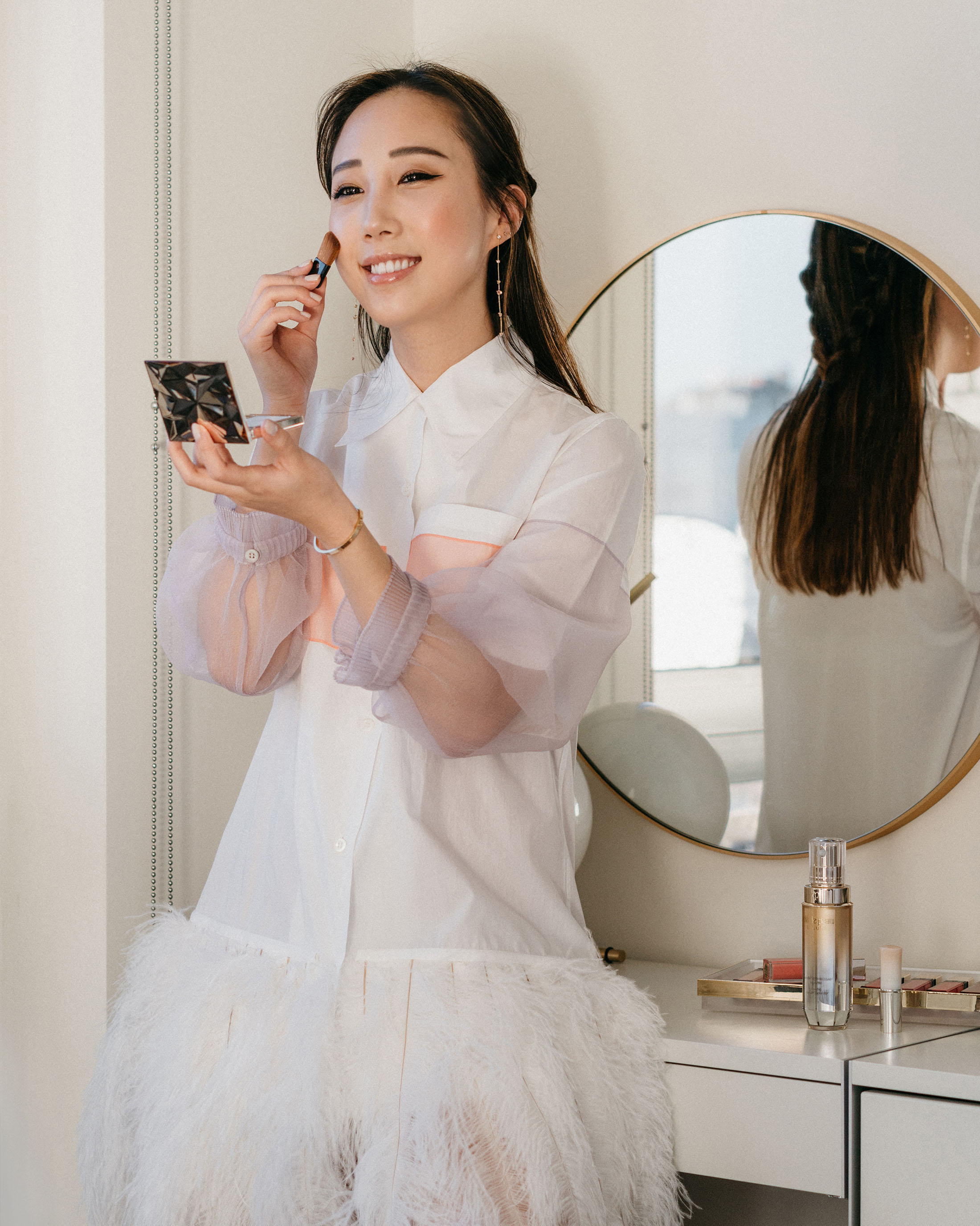 All glowy applying  Clé de Peau Beauté Luminizing Face Enhancer