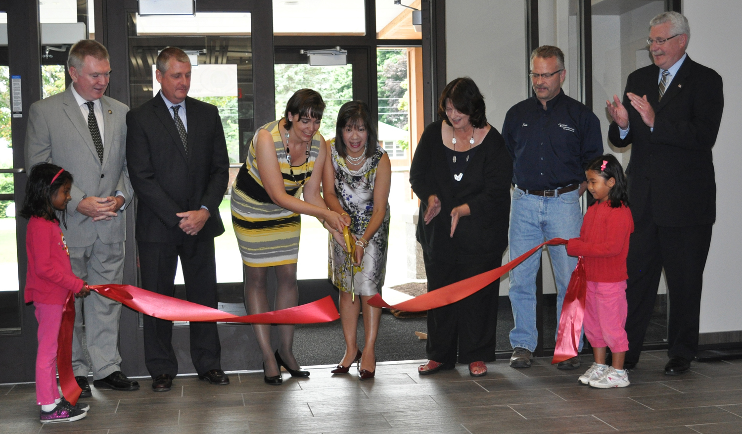 """Participating in the Ribbon Cutting are (left to right):  New York State Assemblyman Mark Johns; Keith Gobel, Canadaigua National Bank; Jacqueline Griebel, WMS Head of School; Garland Nichols, WMS Board of Trustees Chair; Ann Carmody, Webster Chamber of Commerce, Jim Burms, The Nichols Team; and Tony LaFountain, Penfield Town Supervisor. Special thanks to our """"Ribbon Holders,"""" students Celene (left) and Joyce (right)."""