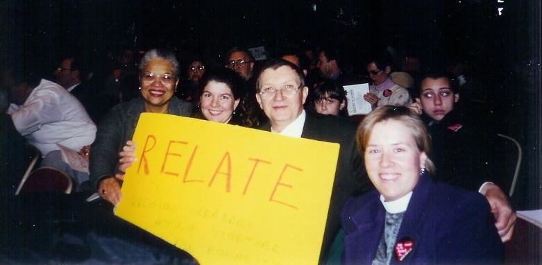 """(1999 - 2002)  Lorelei McClure (then of the Baha'is of Evanston and the National Center), Pastors Stephanie Perdew and Dave Owens (First Congregational Church, U.C.C., Wilmette), and Rev. Heather VanDeventer (St. Augustine's Episcopal Church, Wilmette) at an anti-hate rally at Niles West High School in 2000. RELATE was responsible for the hundreds of """"No Room in My Heart forPrejudice"""" stickers worn by all that day, protesting the KKK."""