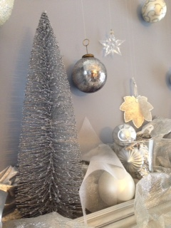 The metallic tree and shimmering fabric were part of last year's silver garden display.  This year, they are adding some glamour to our mantel.