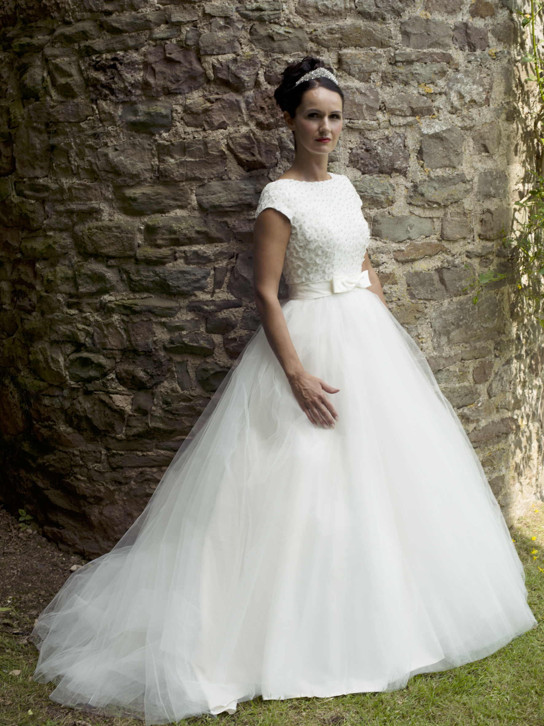 A full skirt withlayers of English netprovidesperfect contrast to the stunning crystal-embellished, cap-sleeved bodice with deep V back detail.