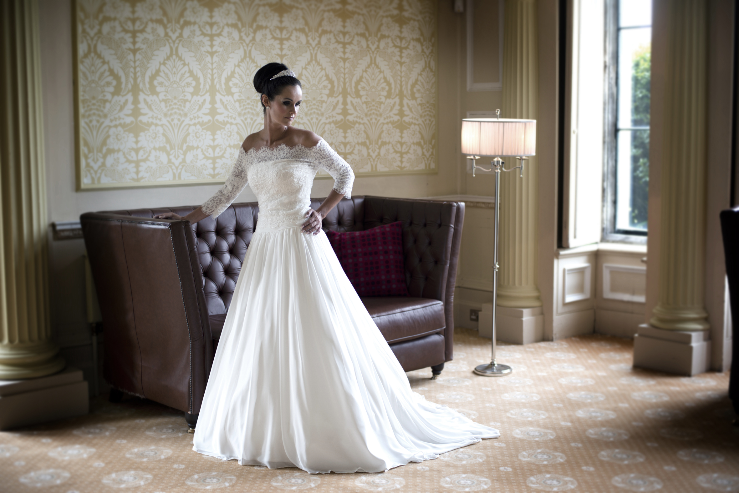 A stunning chiffon ball gown with ruched bodice and lace appliqué detail. The off the shoulder lace jacket is fully detachable offering two different looks.