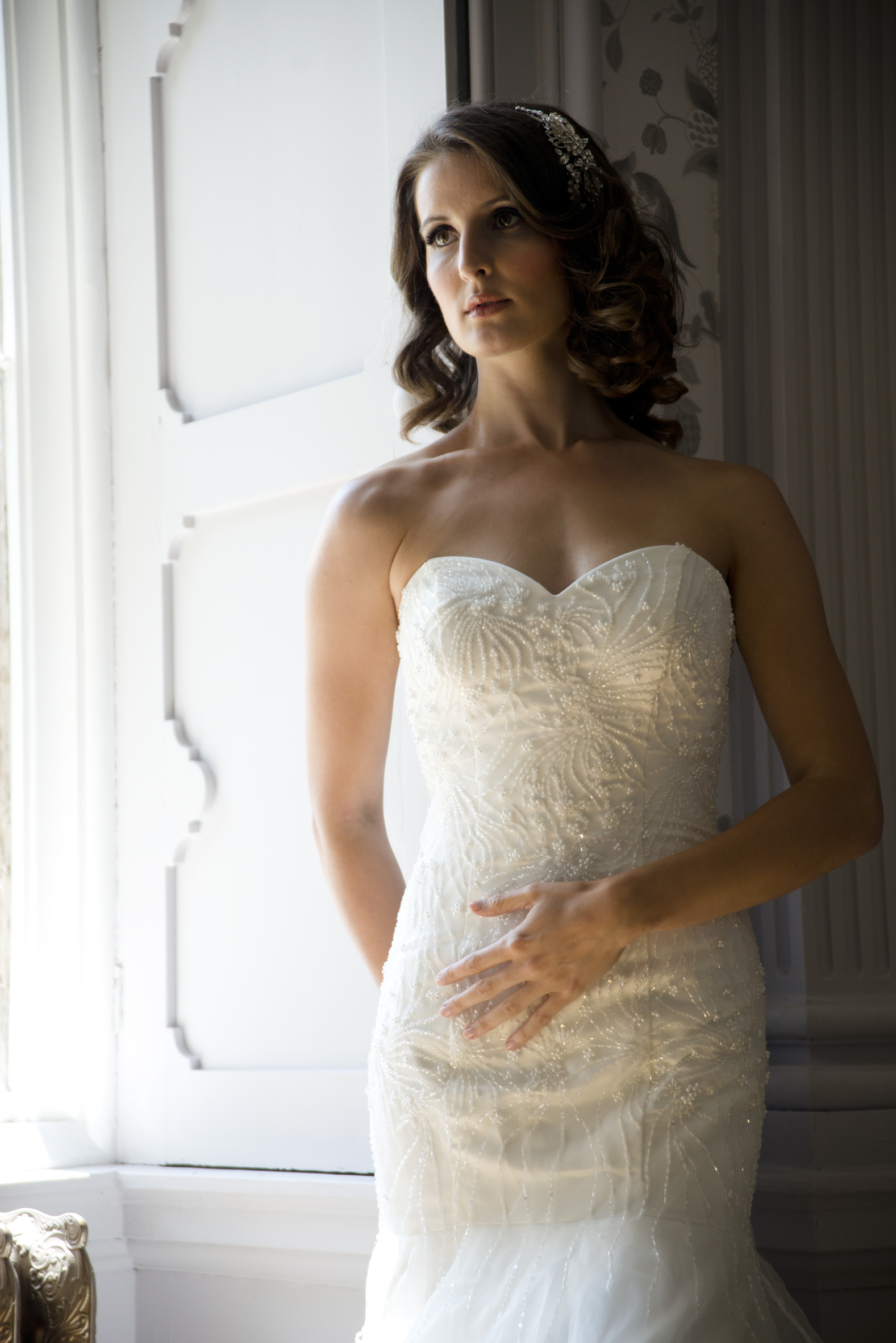 A drop waist gown with fitted bodice and full skirt. The bodice is fully embroidered with delicate beads and crystals.