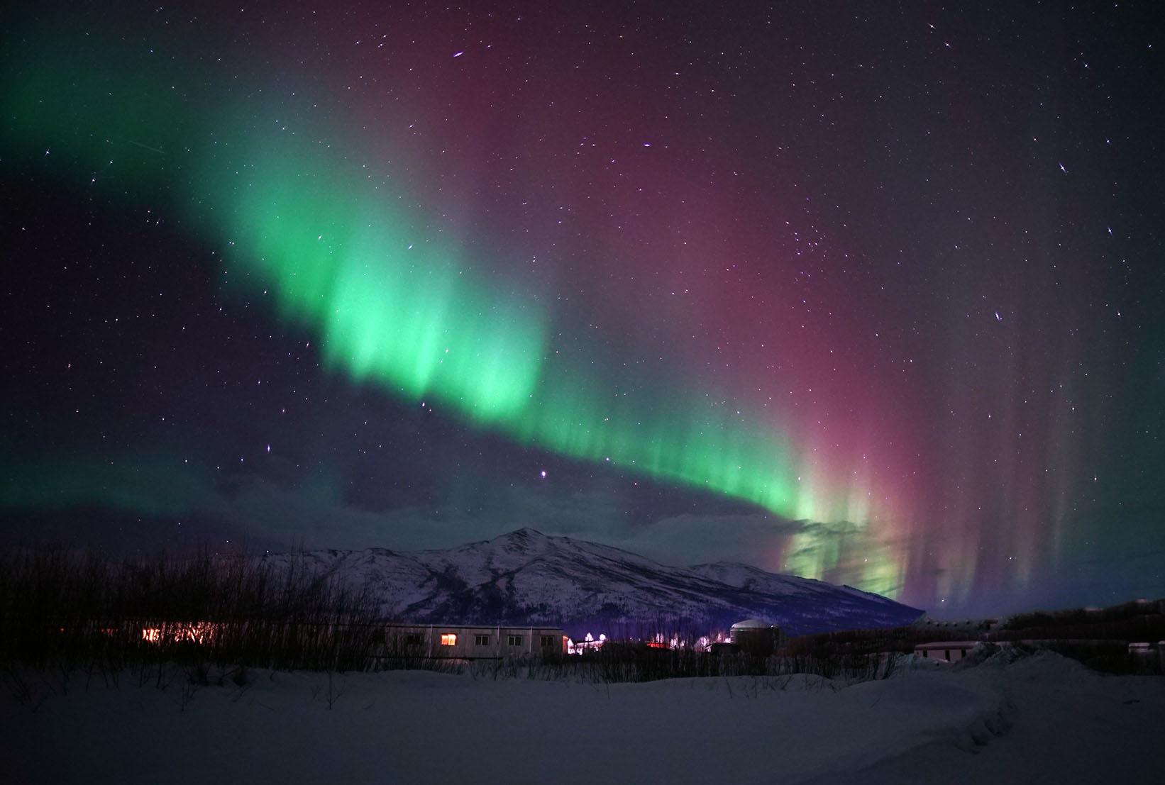 Colorful aurora borealis over Slate Mountain by Kenji Sato.