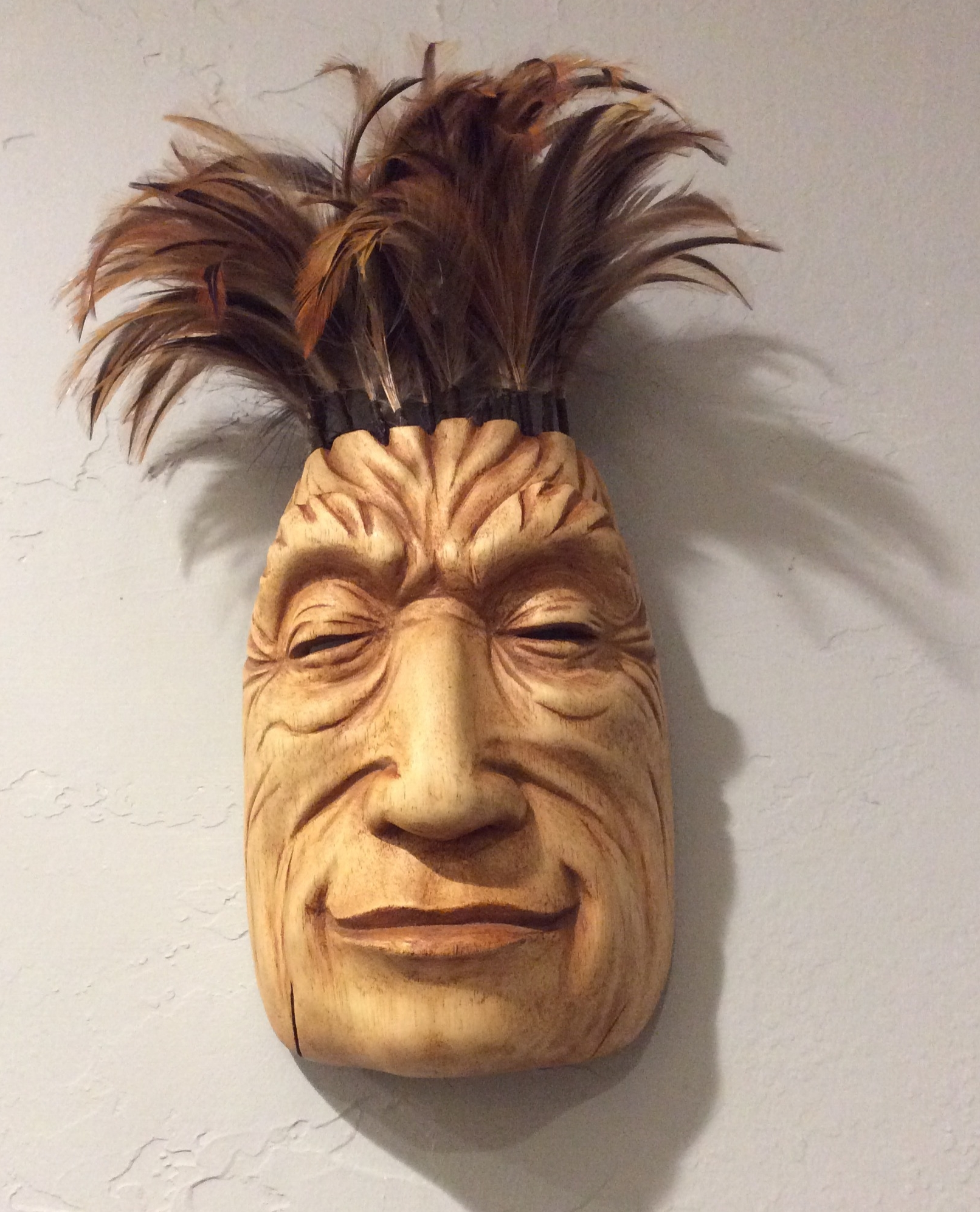 My mask from the second workshop was more playful. I didn't have an image in mind when I was carving but was trying for a peaceful smile. I had lots of fun making the feather duster hair. I actually took apart and reassembled a duster that I had been keeping for the feathers.