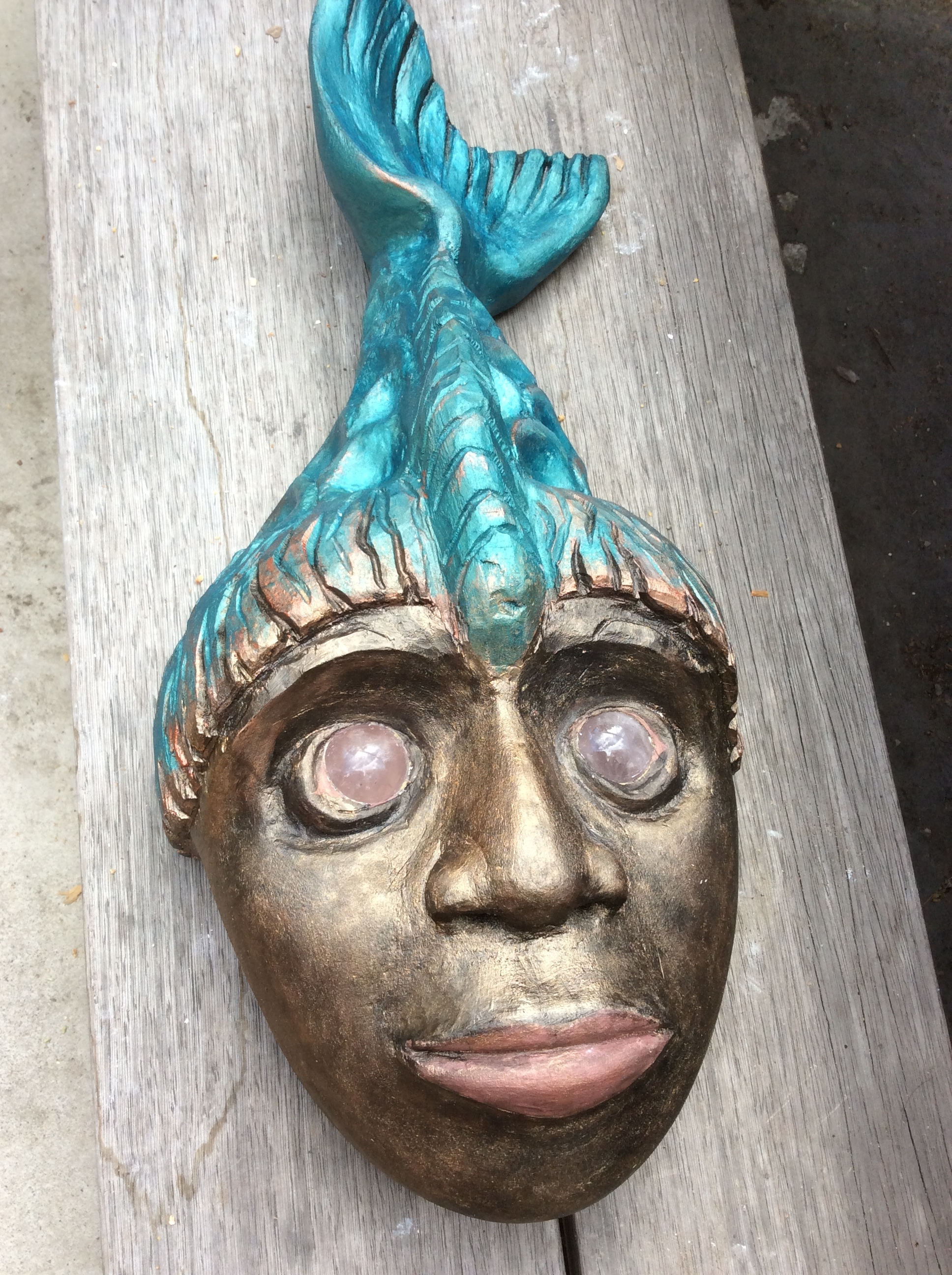 Joy finished her Mermaid mask carved in Basswood.  She used some stone spheres for the eyes so when it is held up to the light they have a soft glow.  She was inspired with the color and it is hard to even tell this is a wood piece.  It has a look of ancient metal.