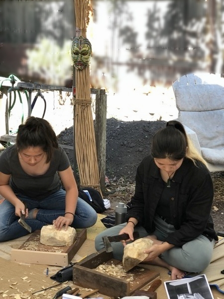 Week one of Balinese mask carving. The first step was to rough out the mask design. Ashley and Twiggy are using the small hatchet to do some of the rougher work. The younger carvers sat Bali style right on the ground.