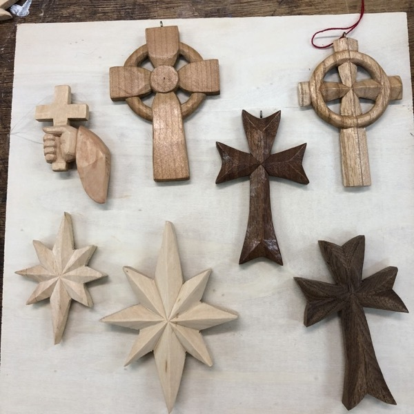 Here are some stars and crosses. The two stars are basswood, the two dark crosses are carved from walnut, the cross in the upper right is carved from butternut, the hand holding a cross is basswood and the cross to the right of that one is cherry. You can see the beautiful knife worked surface.