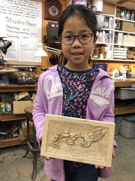 Rosie finished her hummingbird carving. The background is texture punched and the details of the bird and flowers are wood-burned.