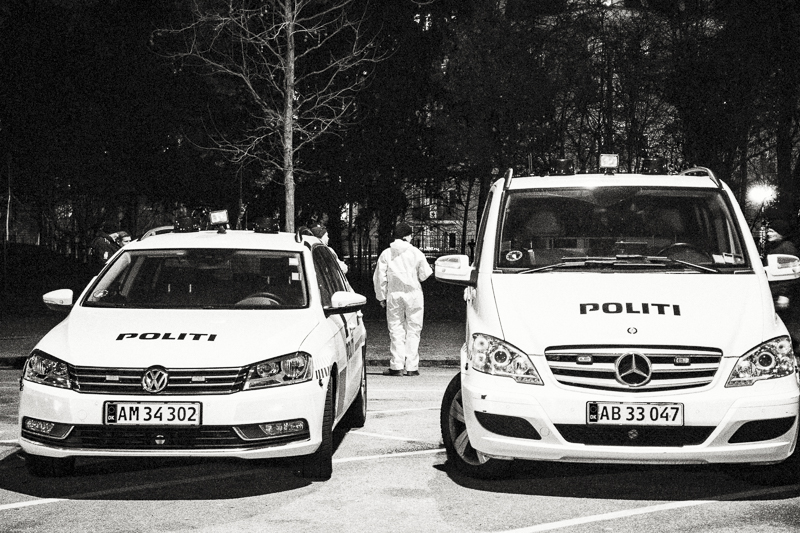 "Saturday 14th 2015 (Evening) - Forensic police stands between two police cars by the Culture Center ""Krudttønden"" (""Powder Keg"") a few hours after the terror attack."