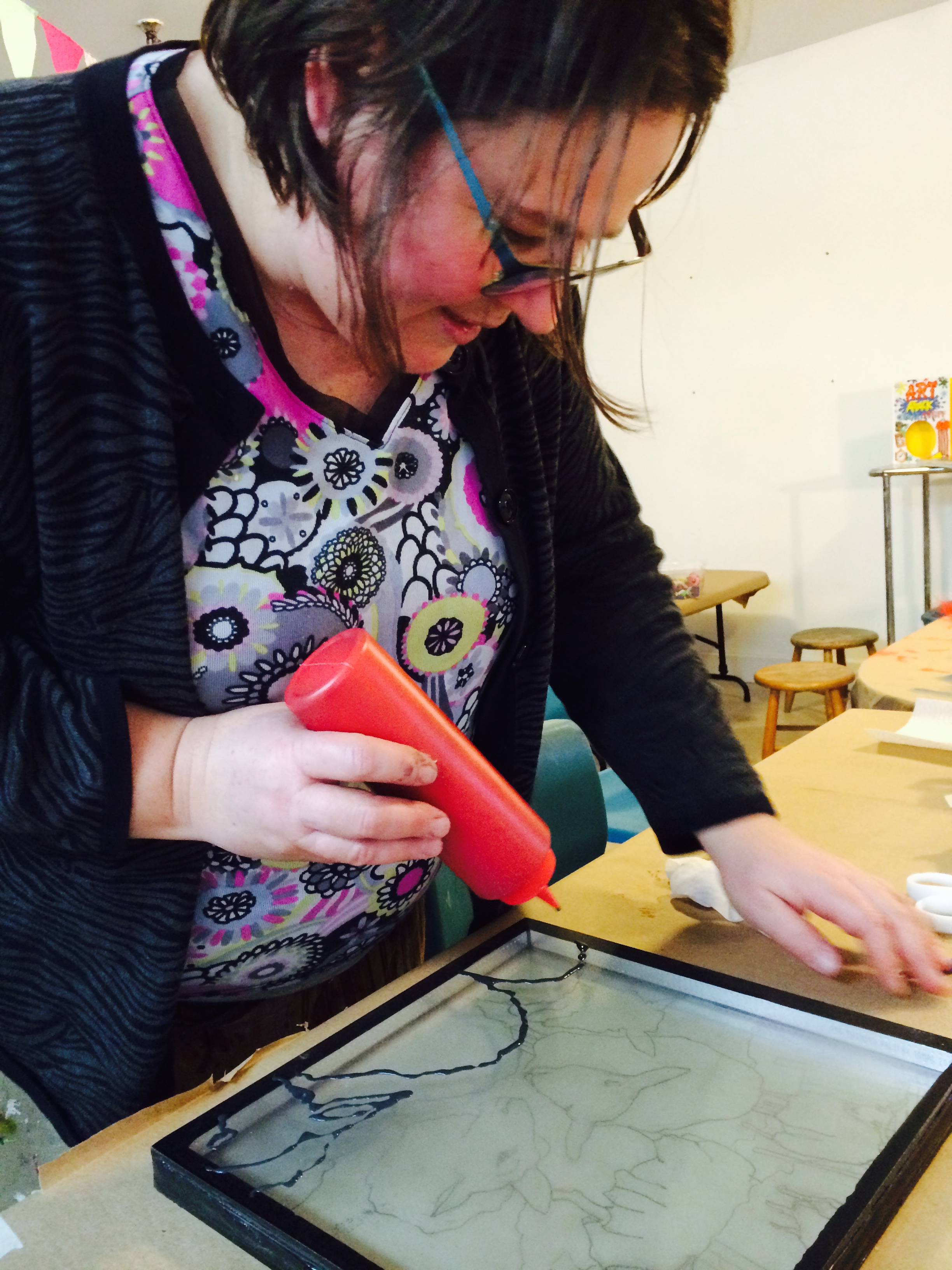 Facilitator Heather is also at work, experimenting with a home-made stain glass paint on glass samples donated by Fowler Bauld & Mitchell.
