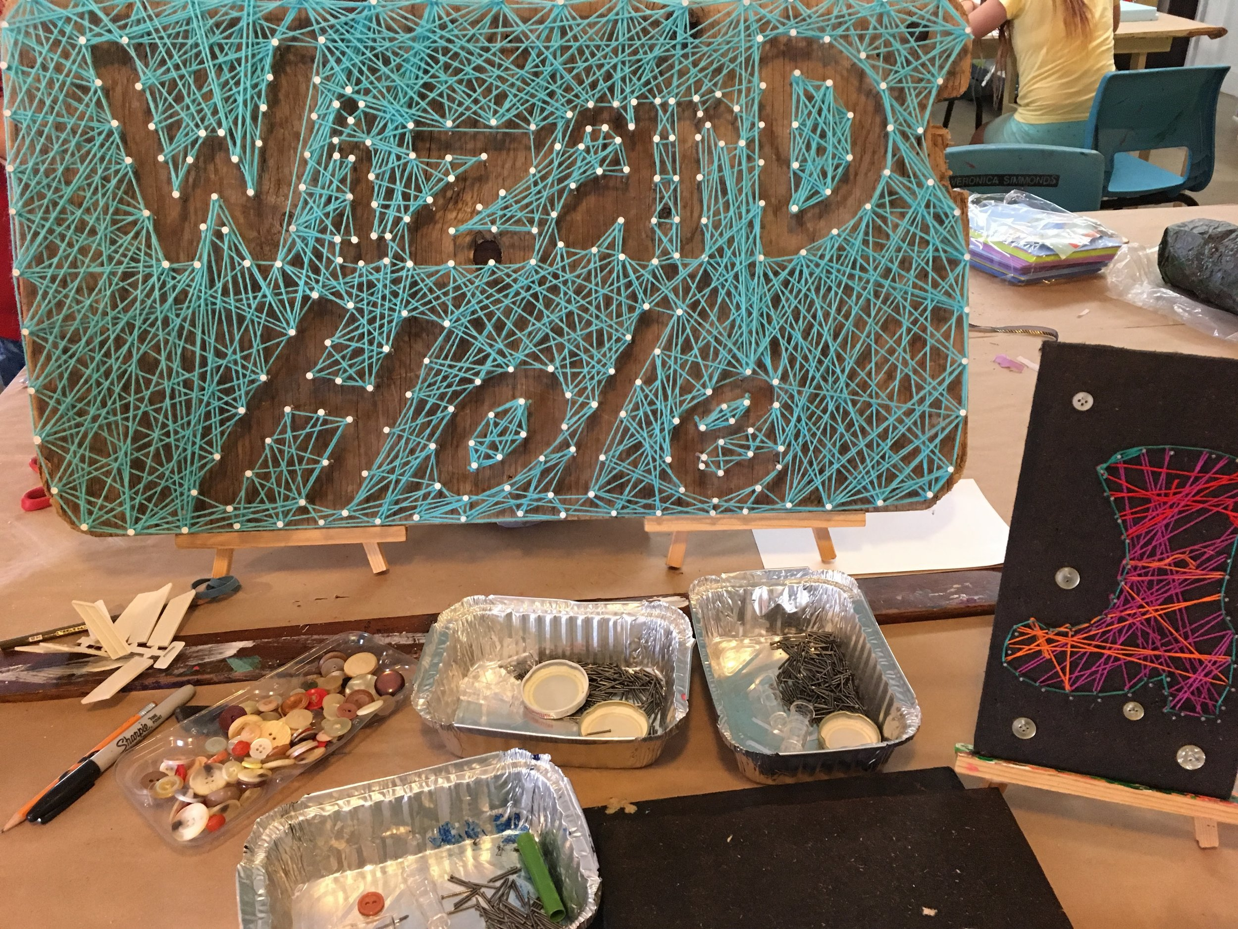 Some days we invent or research really interesting projects to share during Open Studio.  On other days we are rushing to transition the studio from one event to another and we end up looking around for inspiration. Luckily, we share the space with incredibly creative (and weird) folks like the wizards (aka ceramic artists).  Thanks for sharing this awesome sign with us on our string art exploration day!