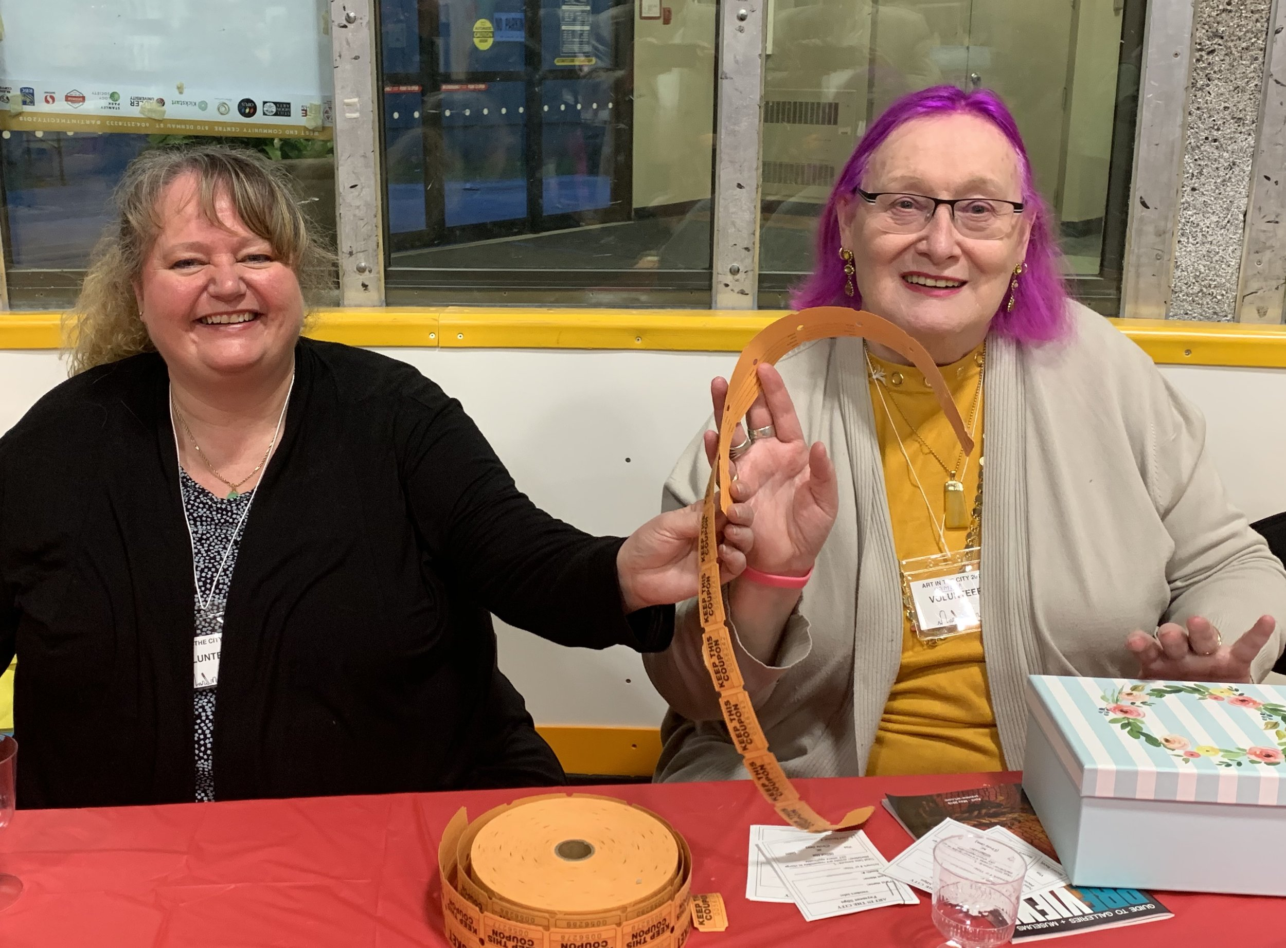 West End Community Centre business manager Debbie Coulson (left) and longtime volunteer and board member Pamela Leaman greeting guests at Art In The City … and sharing drink tickets!