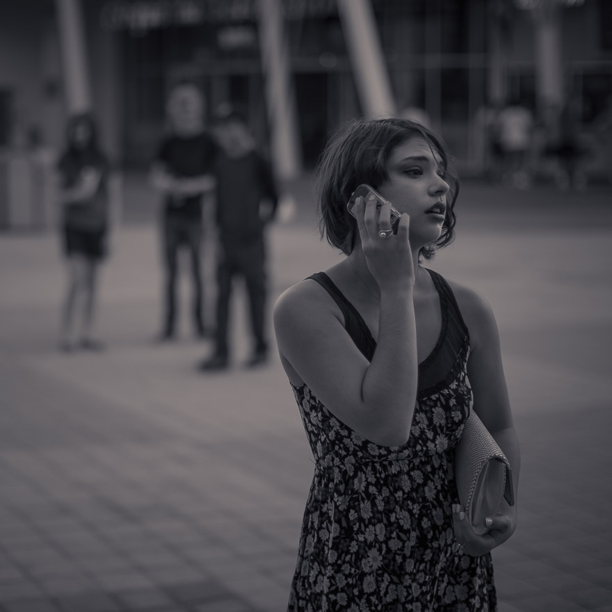 A young woman talks on her cell phone while waiting. © Jeremy Allen