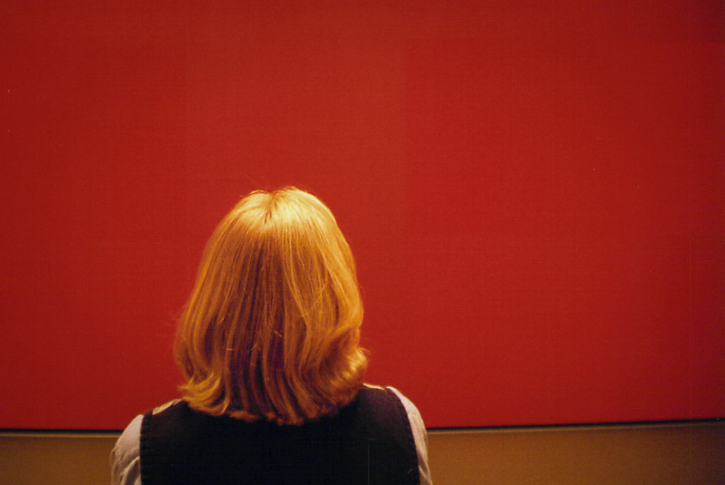 Blonde woman stands in front of and faces large red painting