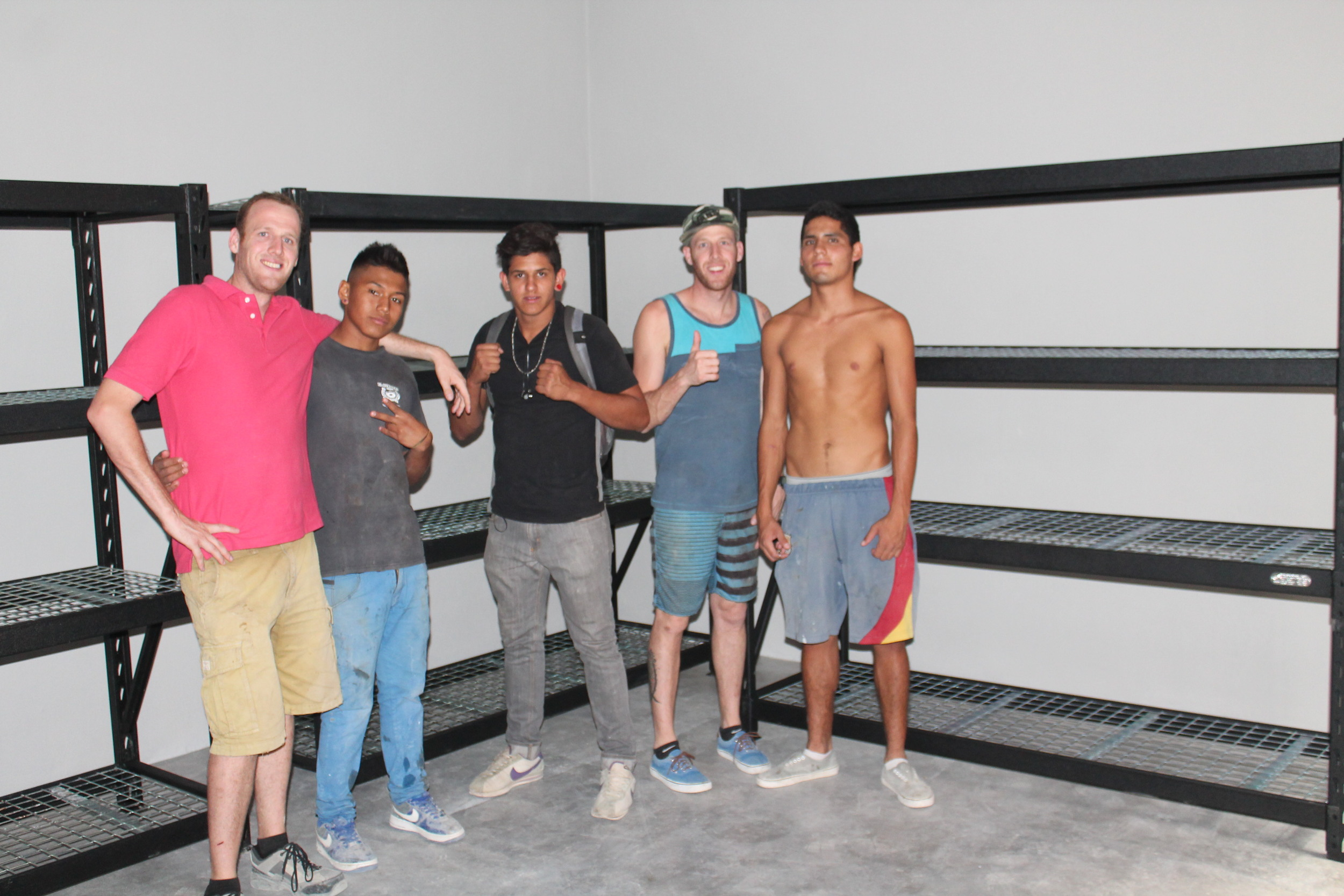 Three of our youth, Eduardo, Fernando, and Chino (from left to right), in the storage room.
