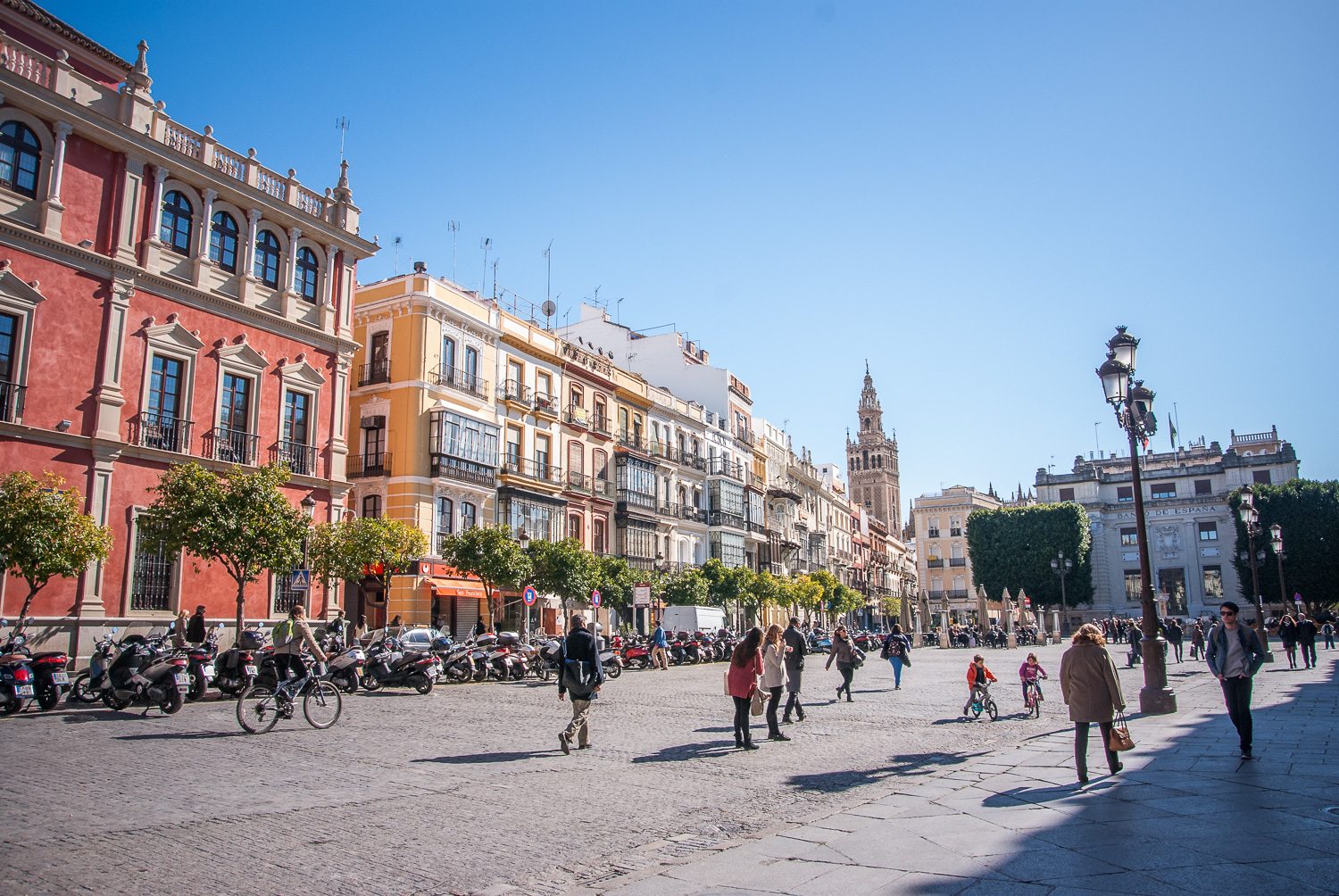 San Francisco Square (  Plaza de San Francisco) with Giralda Tower (ancient minaret of the old mosque of Sevilla) The pink building was the Royal Court in the 16th century