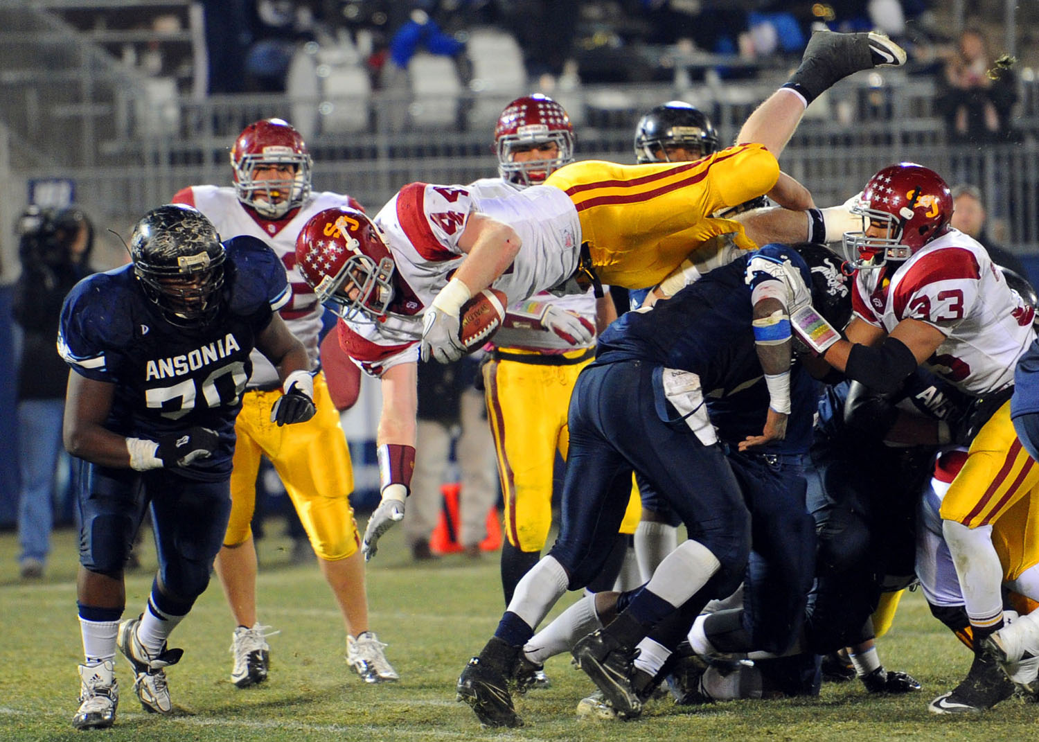 St. Joseph's Tyler Matakevich dives over Ansonia's defense to score a touchdown during the Class S State Football Championship game in East Hartford on December 11, 2010.