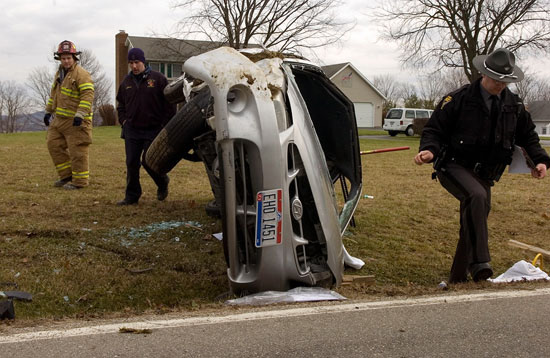 Trooper David Johnson, right, walks around a Hyundai that flipped Thursday on Egypt Pike. The driver of the car was partially ejected during the crash.
