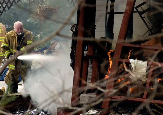 A Green Township Firefighter smokes a cigarette as he works to extinguish a fire in Williamsport. The fire destroyed John Rankin's historic home.