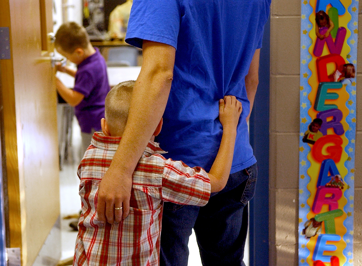 A boy holds on to his father as he is dropped off for the first day of Kindergarten.
