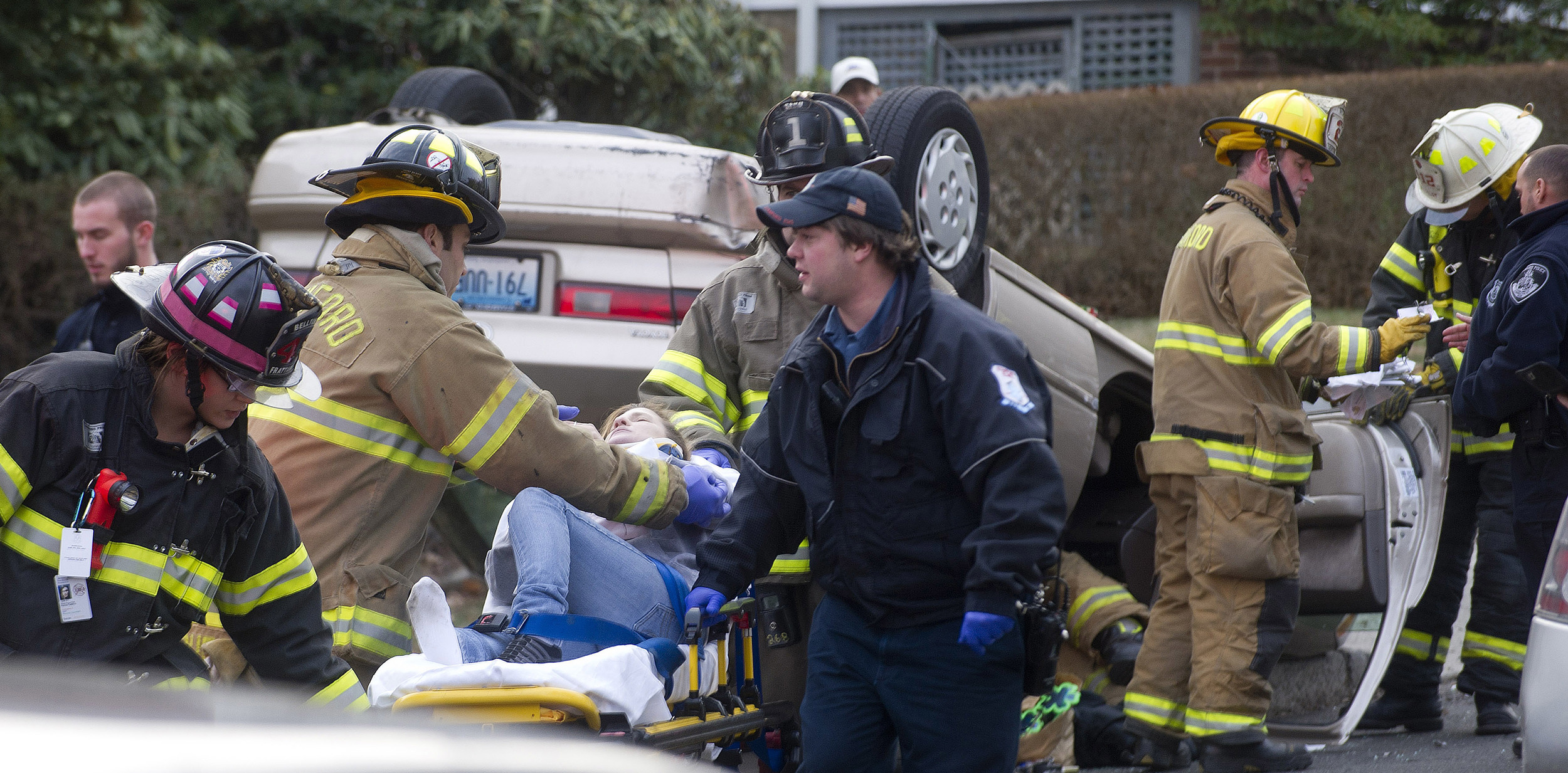A woman is taken to an ambulance on a stretcher as her overturned Toyota sits on the sidewalk behind her after an accident on Colonial Road on Wednesday, January 1, 2014.