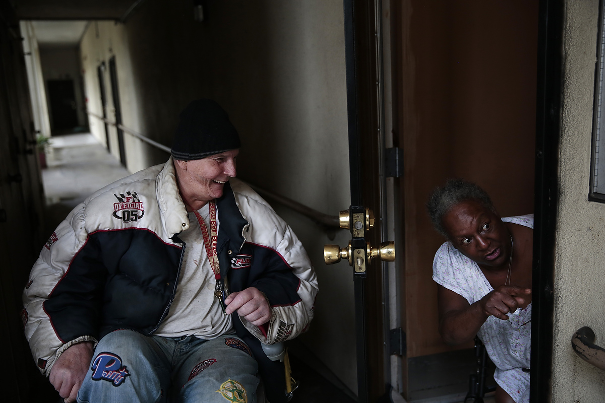 Resident Everett Dennis Lewis, 62, laughs at friend and fellow resident Rhonda Marshall, 59, as she talks with her neighbor at the Hacienda housing complex in Richmond, California, Friday, February 6, 2015.
