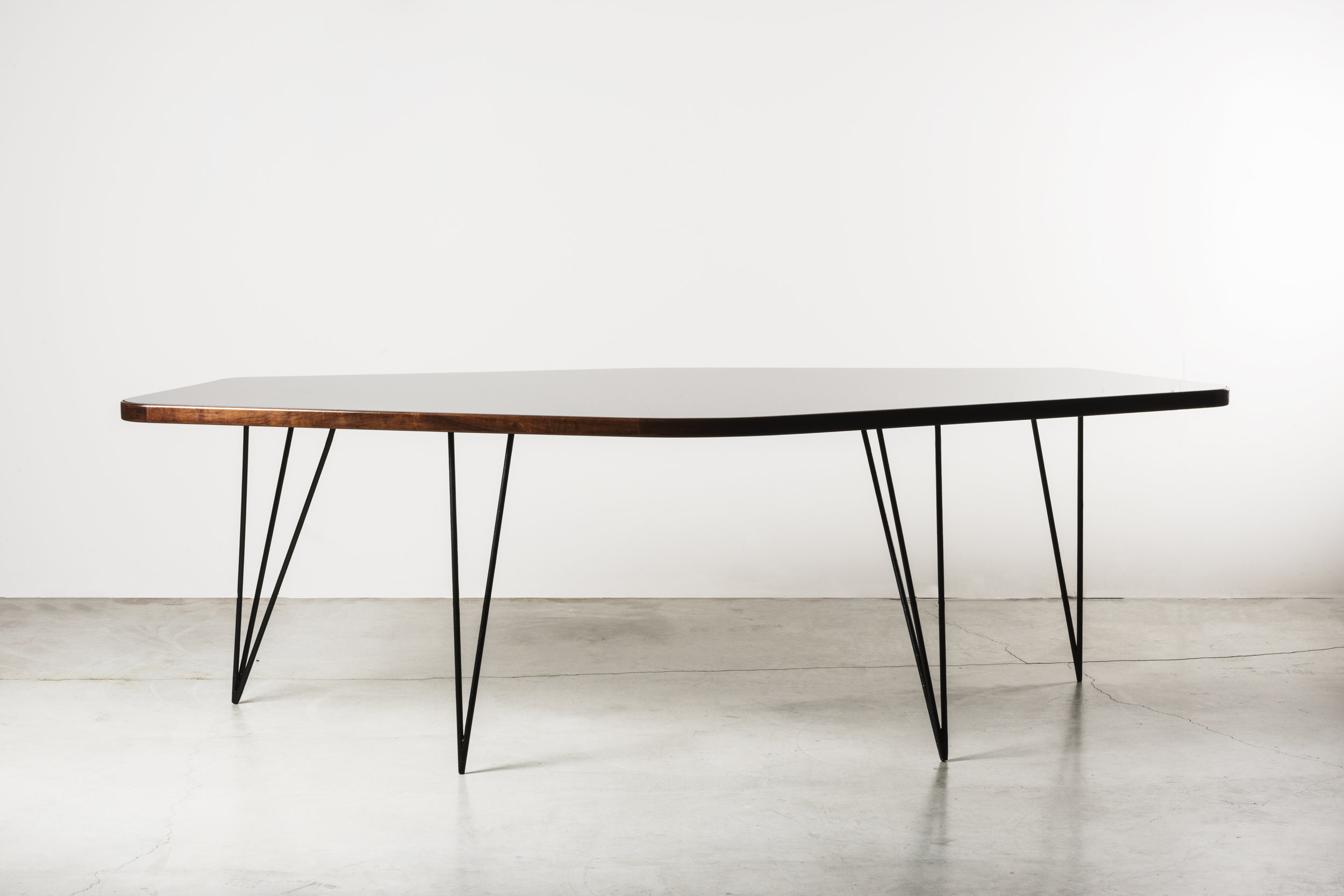 Poligonal table, Brazil, 1958  Design: Joaquim Tenreiro Ebonized jacaranda wood, painted steel, backpainted glass  size: 234 x 108.6 x h74 cm / 92 x 42.8 x h 29 in  ⓒ Nilufar Gallery