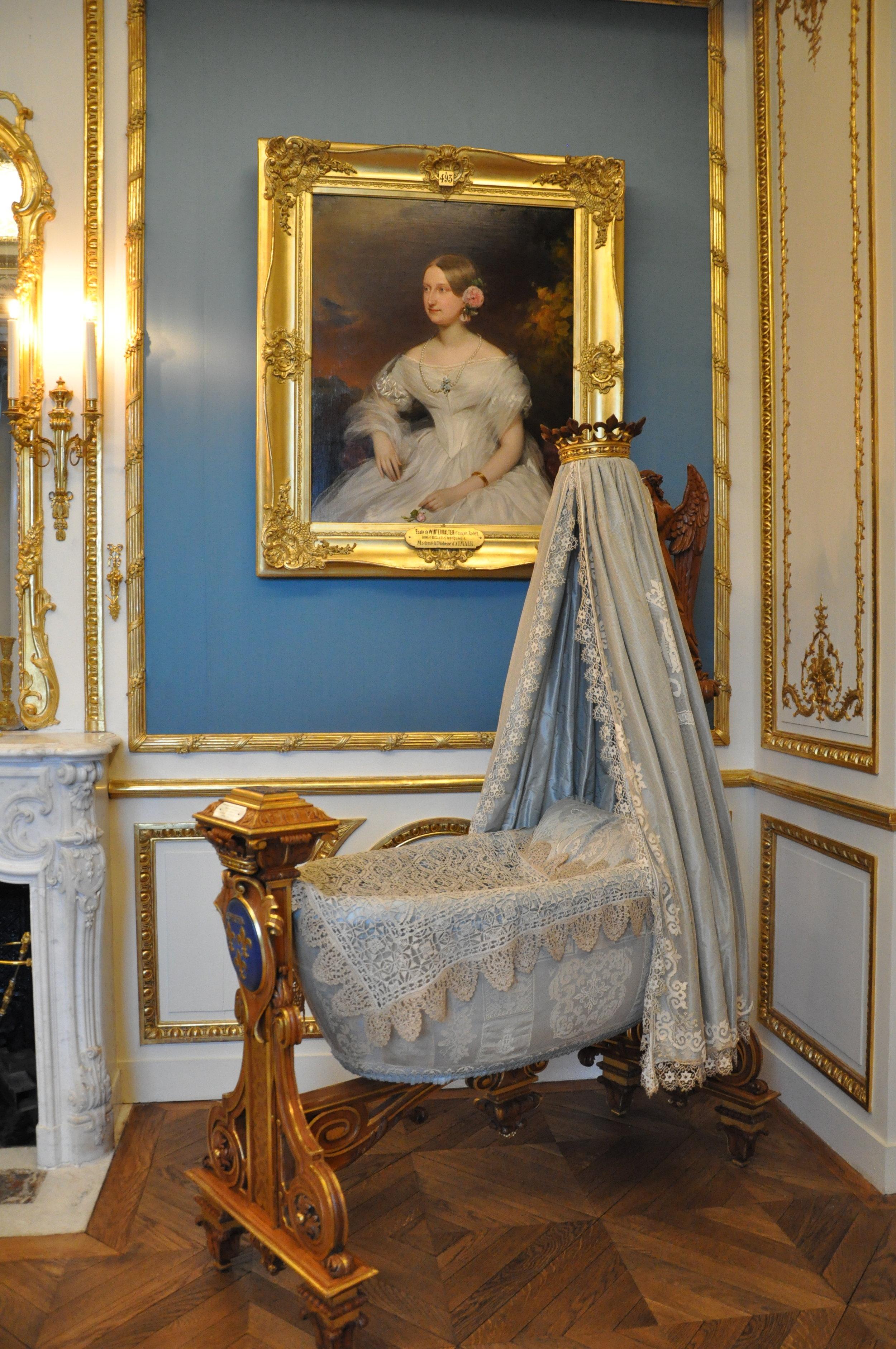 Duke of Guise's cradle in the Duchess' bedroom with portrait of his mother, Marie-Caroline-Augusta de Bourbon-Siciles, Duchess of Aumale (1822-1869) by Franz Schrotzberg © Grand Palais Domaine de Chantilly