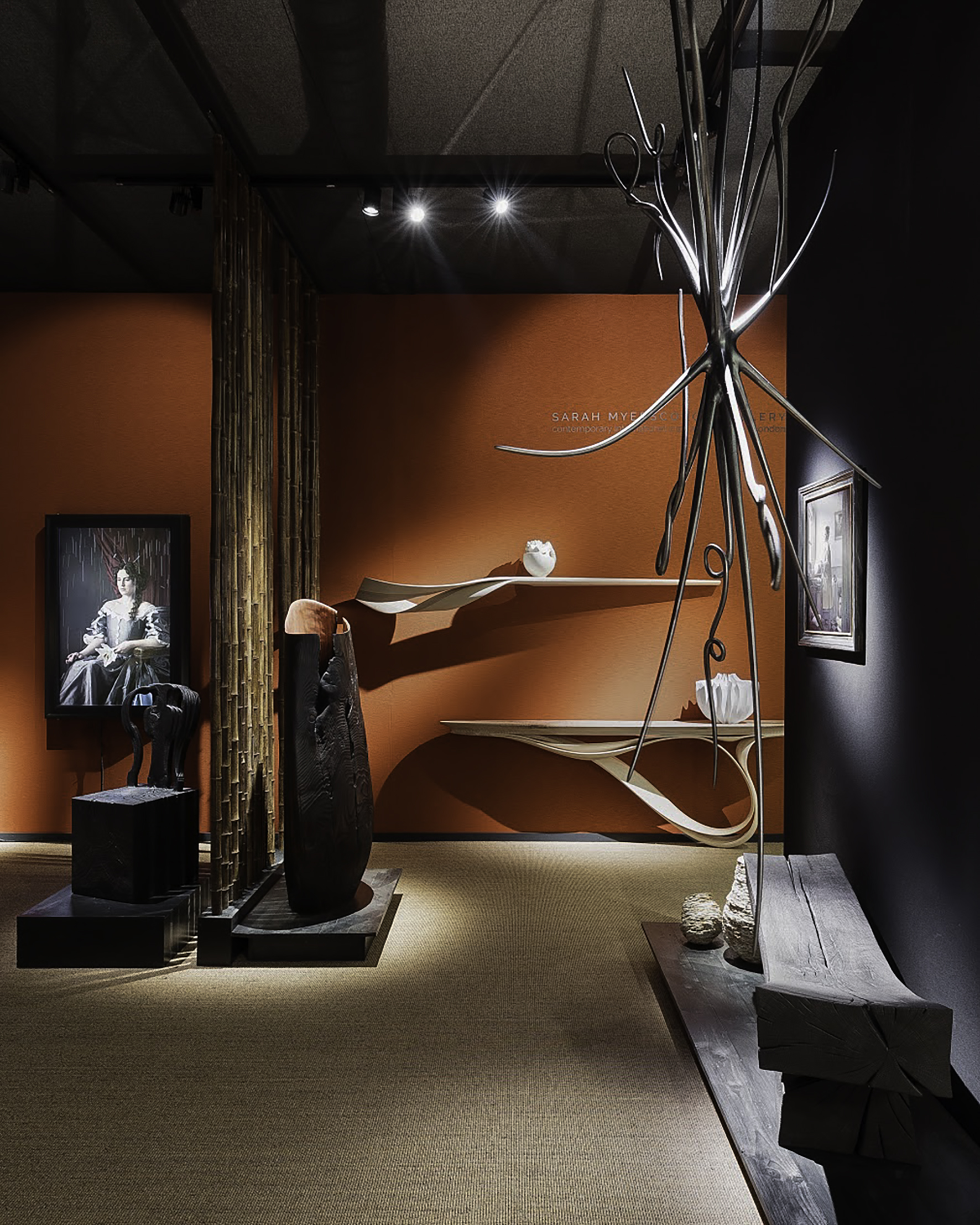 Sarah Myerscough Gallery at Masterpiece London 2019 ⓒ Ollie Hammick  On display  Ascender  sculpture by Christopher Kurtz (suspended, foreground),  Enignum  consoles by Joseph Walsh (background) ,  Scorched Embrace  Table, by Jim Partridge and Liz Walmsley and  Down Pour  Video piece by Maisie Breoadhead (background, left)