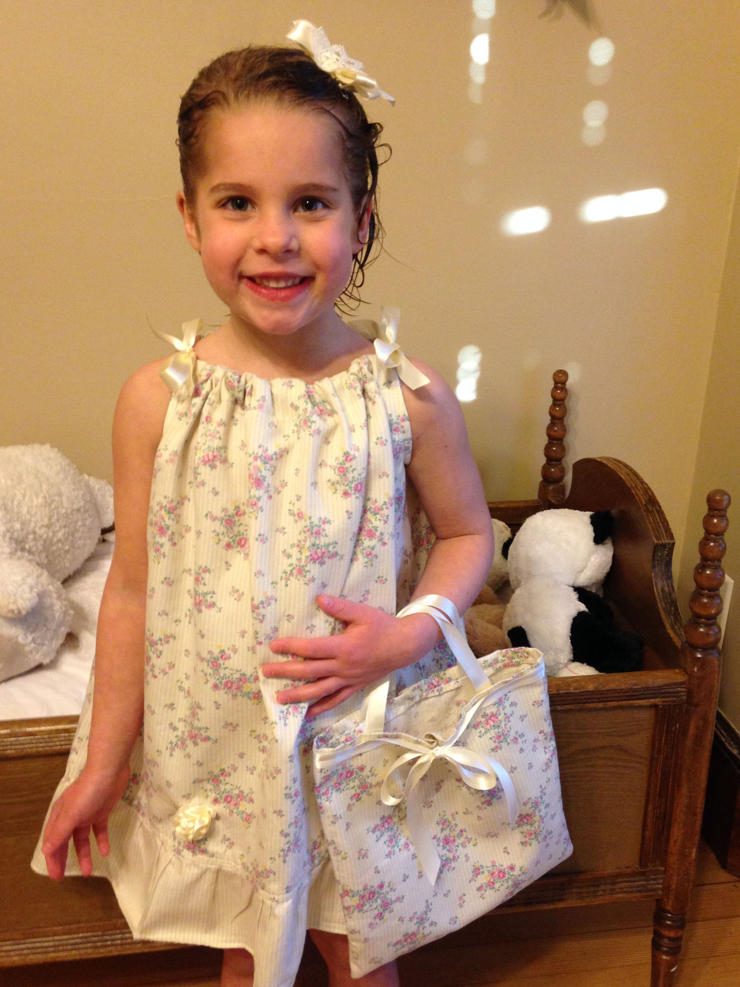 Pillowcase dress on the sweetest girl with a matching purse and rosettes made by her mom.
