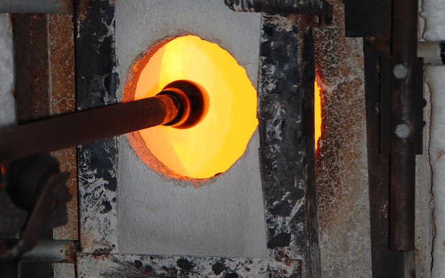 """Rick is reheating the hot glass during the shaping process, in the """"glory hole"""". The Day tank with Rick Strini"""