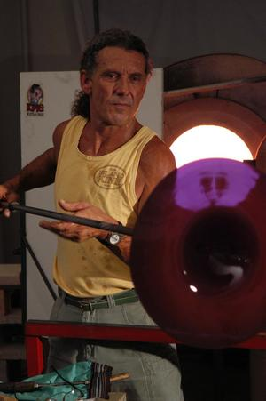 "Spinning a ""rondel"" in front of the ""Glory Hole"", the reheating kiln in which the master works."