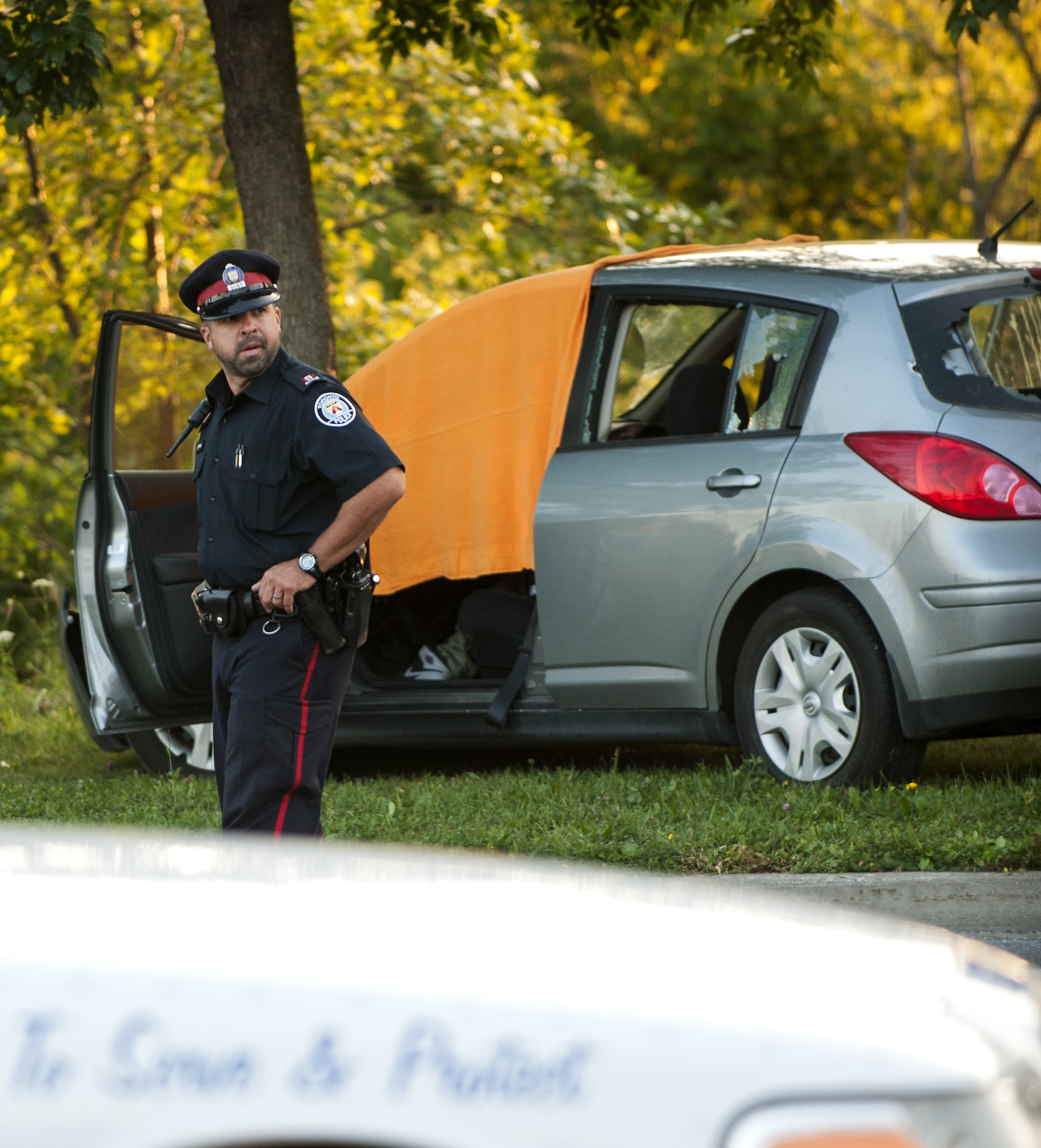 A Toronto Police officer watches the growing crowd at a shooting scene at Jane St and Eglinton Ave on August 8, 2014. The passenger was rushed to hospital in critical condition, while the driver was pronounced dead at the scene.