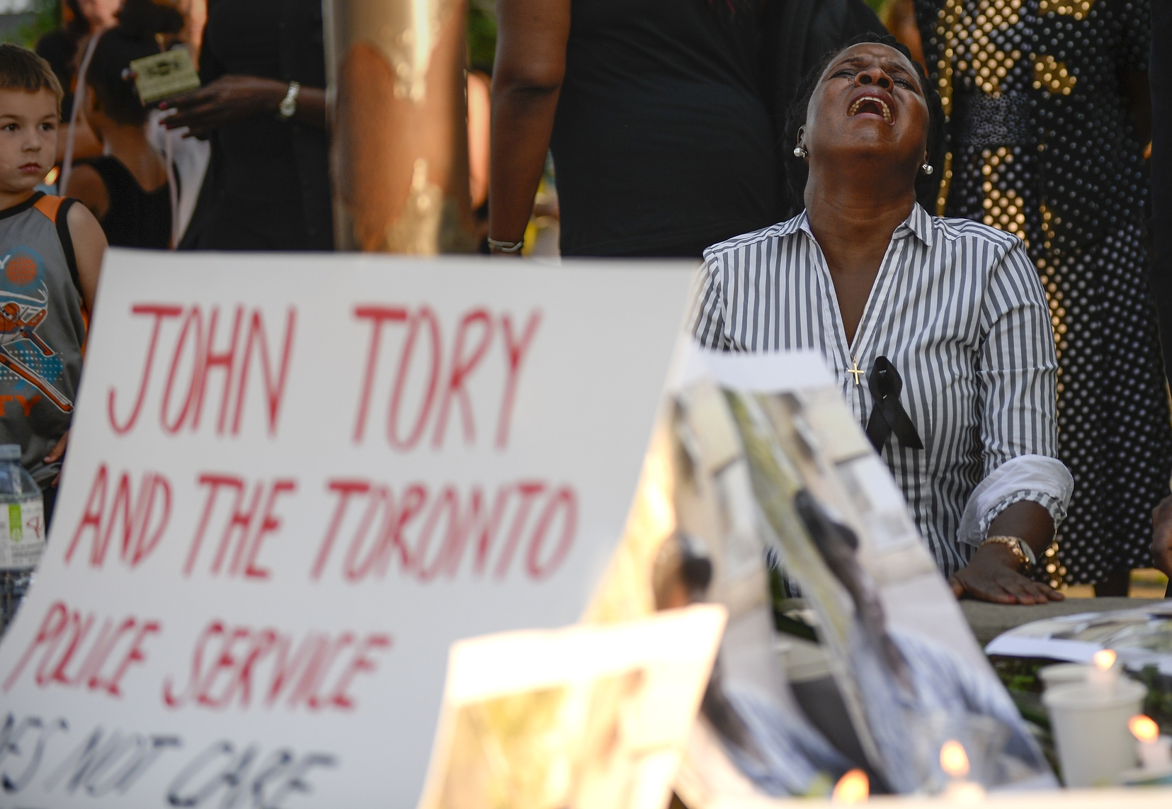 A woman cries during a vigil at  Eglinton Gilbert Parkette held for Andrew Loku on Friday July 10, 2015. Loku was shot and killed by police on July 5, 2015.