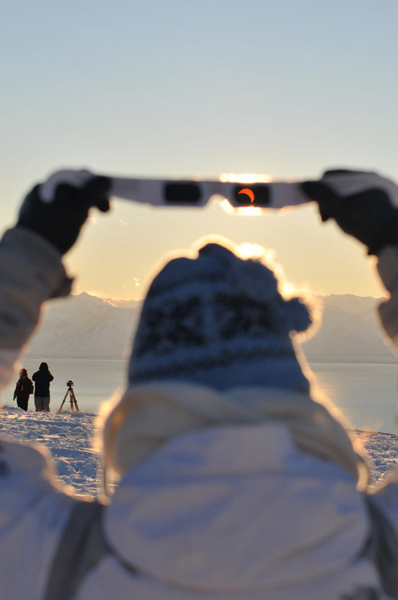 My friend holding her eclipse shades to see the setting sun about halfway eclipsed during the 2010 TSE in El Calafate, Patagonia, Argentina