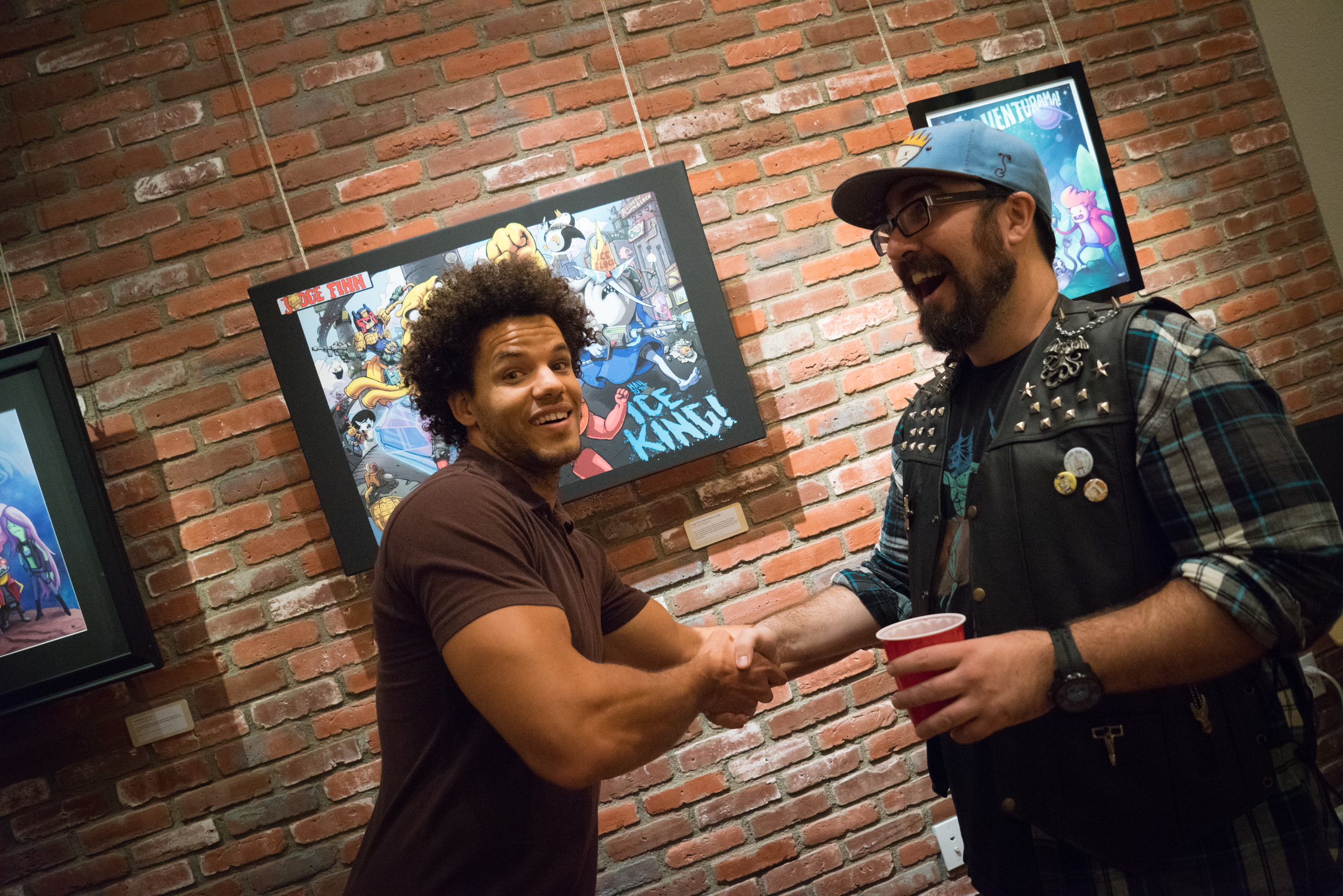 """Artist of """"Judge Finn: Hail to the Ice King!"""",Kevin Maginnis, greeting a gallery patron during the exhibit."""
