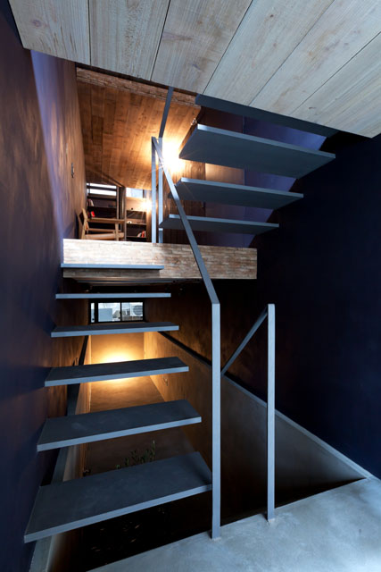 Both staircases consist of steel treads without supporting risers, and slender handrails allowing light to filter through.