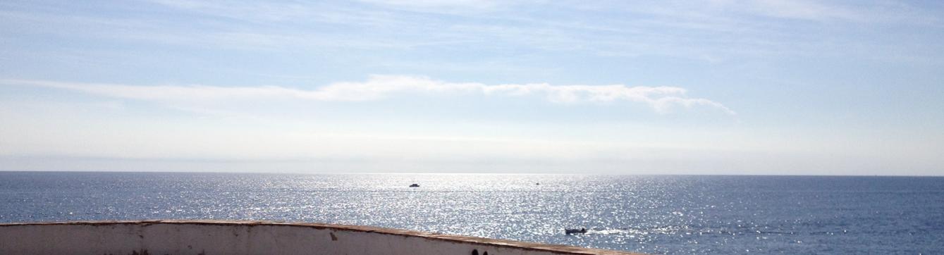 EL MERIDIANO DE LUZ ABANDONA EL CONTINENTE EUROPEO EN EL MAR MEDITERRANEO POR EL FARO DE PALAMÓS (ES) //  en la hora real del mediodía con la espalda hacia el faro se puede observar cómo el sol refleja su luz sobre el mar hasta el horizonte en una línea ancha norte-sur en el meridiano de luz