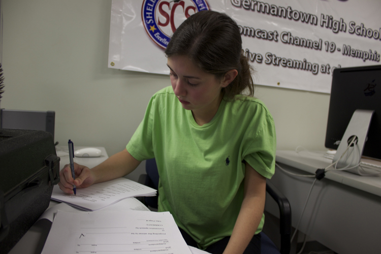 US House anchor Haylay Bardos finishes up her report script. Bardos spoke with area teens about the importance of compromise in light of the perception that the US congress can't seem to do so.