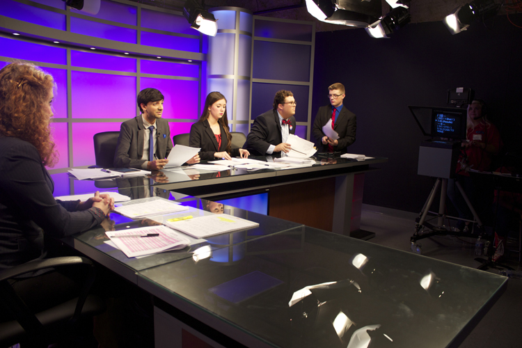 Will Alton waits for an open seat on the anchor desk.