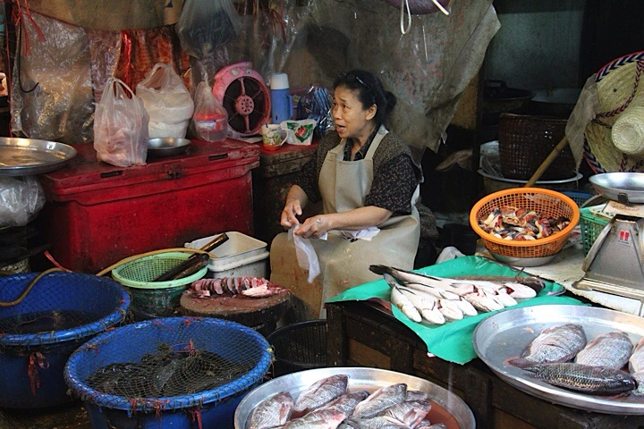 Woman chopping live fish