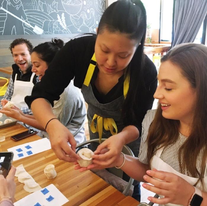Irene Li teaching a dumpling student how to fold roses