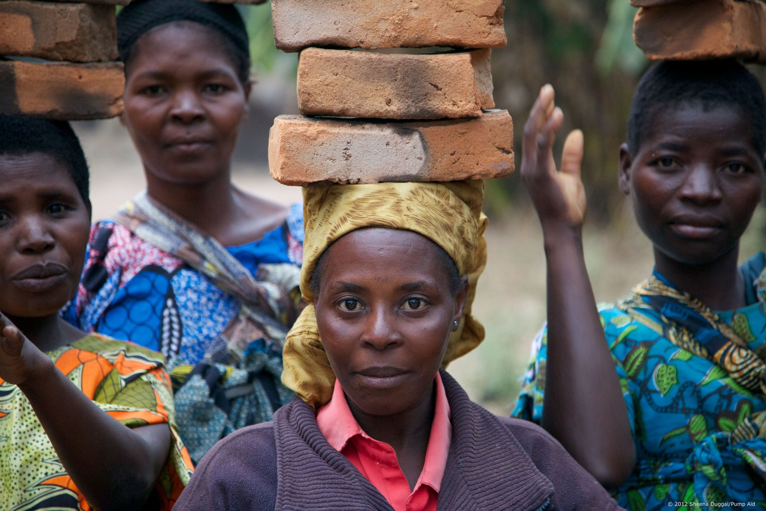 Brick Ladies Malawi 2012  Women carrying bricks for lining a muddy water well.
