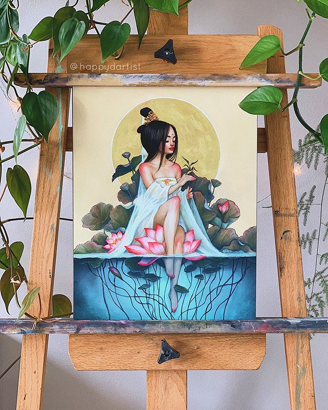 "(FUN FACT: the painting in the first image is actually a print! 😉) Finally sharing some better photos of my painting titled ""Mercy"", who is inspired by the Chinese version of the Goddess of Mercy 🎨🌿 She is often depicted sitting on top of a lotus flower wearing a long white gown + veil with a willow leaf in her hand. I wanted to create a more ""human"" version of this goddess who is taking a vacation from all her deity duties so that she can just chill with her feet in the water and explore her playful side 🌸❤ . ✨20% OFF PRINTS (🔗 IN BIO) ✨ . . . . . . #oilpainting #studio #workspace #artstudio #plants #painting #portrait #artistsofinstagram #surreal #fantasy #watercolor #acrylic #coloredpencil #drawing #sketch #sketchbook #realism #semirealism #magical #chinese #contemporaryart #roomdecor #interiordesign #bohodecor #cozy #pond #goddess #whitedress #lotus #waterlily"